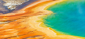 Grand Prismatic pool in Yellowstone National Park with tourists walking on the wooden boardwalk